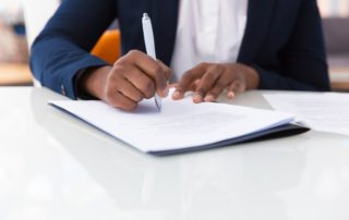 Close-up of African American businesswoman signing contract