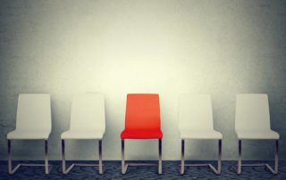 Row of white chairs and one red in the middle