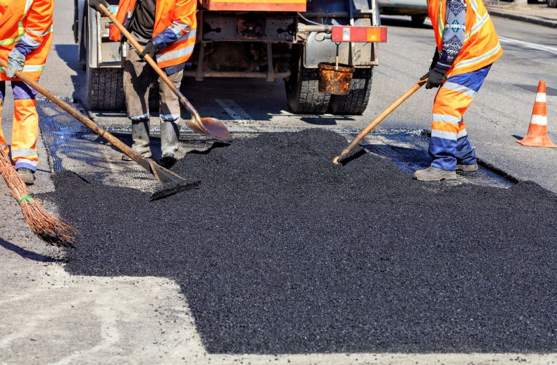 The working team smoothes hot asphalt with shovels by hand when repairing the road