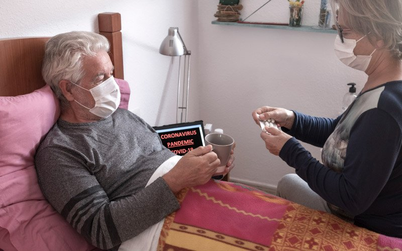 Sick elderly man of COVID-19 lies in bed at nursing home wearing medical mask while wife takes care of him