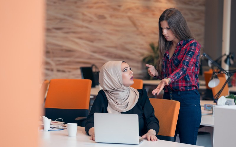 Worried Arabic businesswoman wearing hijab receiving a notification from a colleague in her workplace
