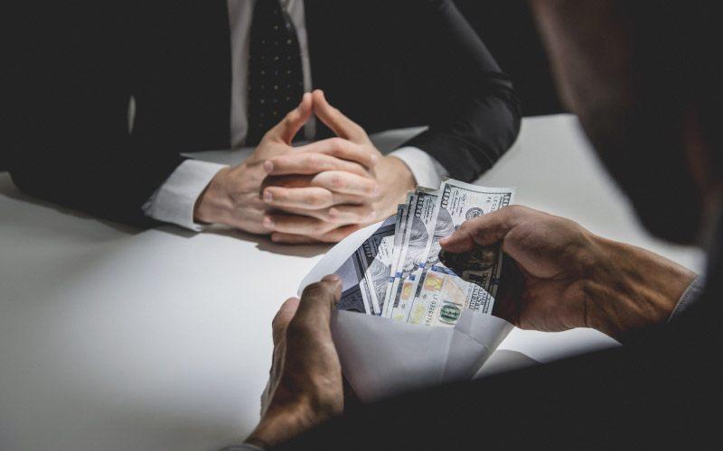 Businessman receiving bribe money, US dollars, in an envelope