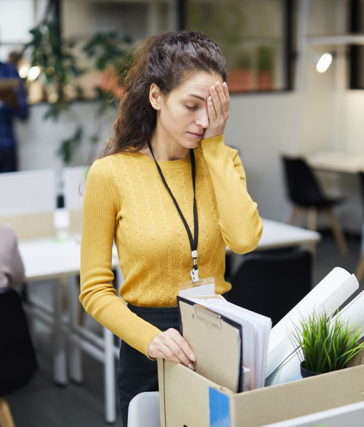 Frustrated young woman in yellow sweater standing at table and touching face with hand on her face while packing stuff in office after layoff