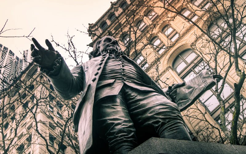 Upward view of a statue of Benjamin Franklin with tree branches and buildings on background