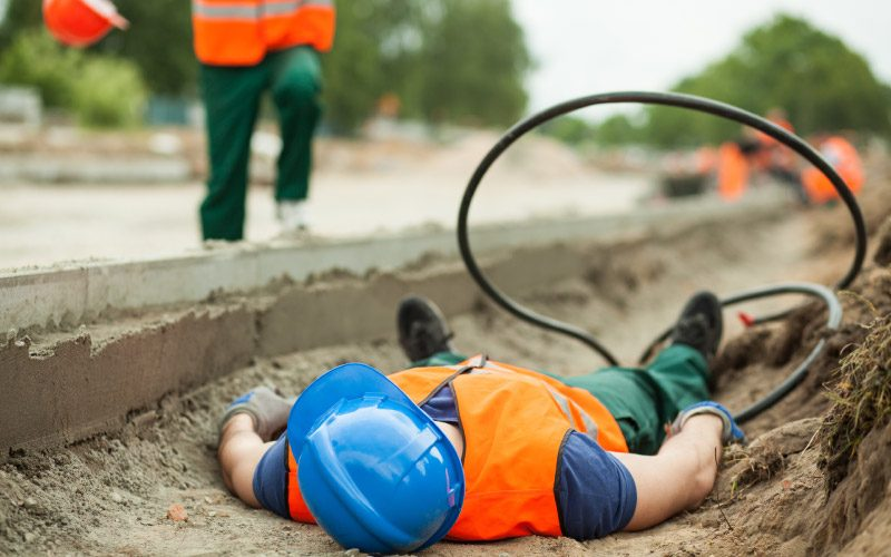 Construction worker injured at construction site, laying unresponsive on the ground