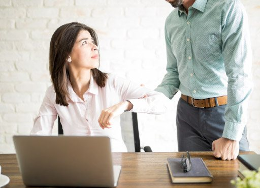 Abusive boss holding the arm of a woman with violence while she looks upset