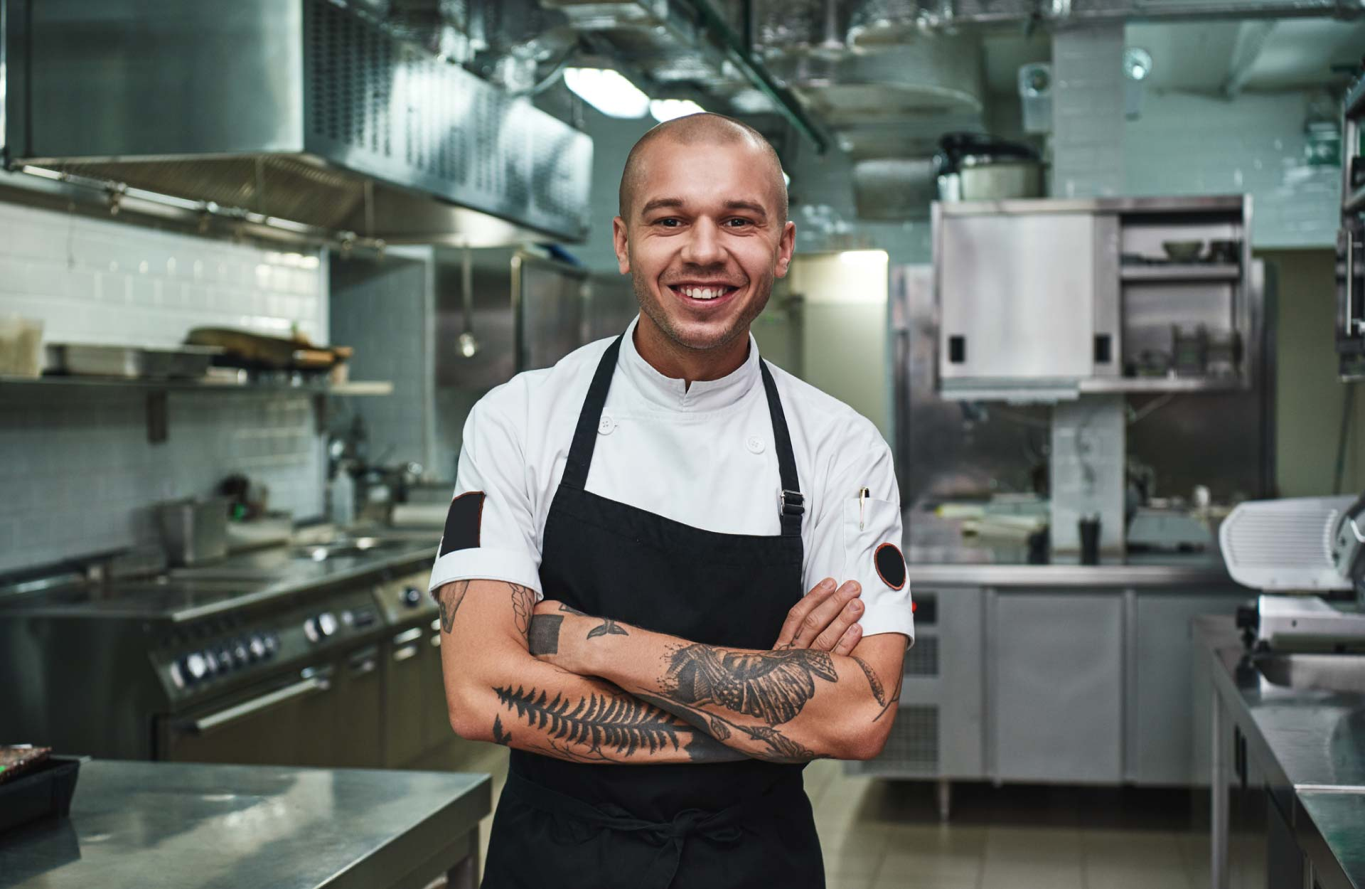 Cheerful young chef in apron keeping tattooed arms crossed and smiling while standing in a restaurant kitchen