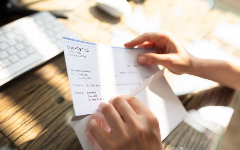 Close-up of an employee's hand opening envelope with paycheck over wooden desk
