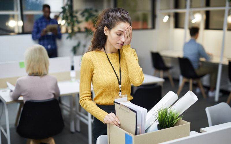 Frustrated young woman in yellow sweater standing at table and touching face with hand on her face while packing stuff in office after dismissal