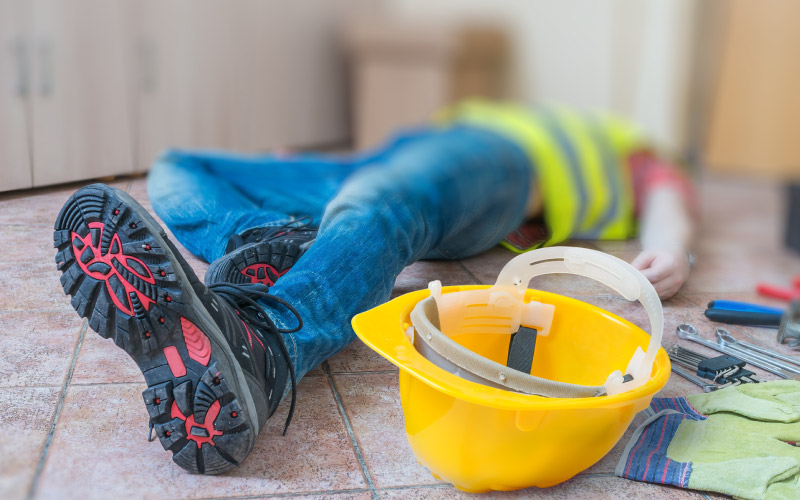 Leg and yellow helmet of injured worker at work lying on the floor