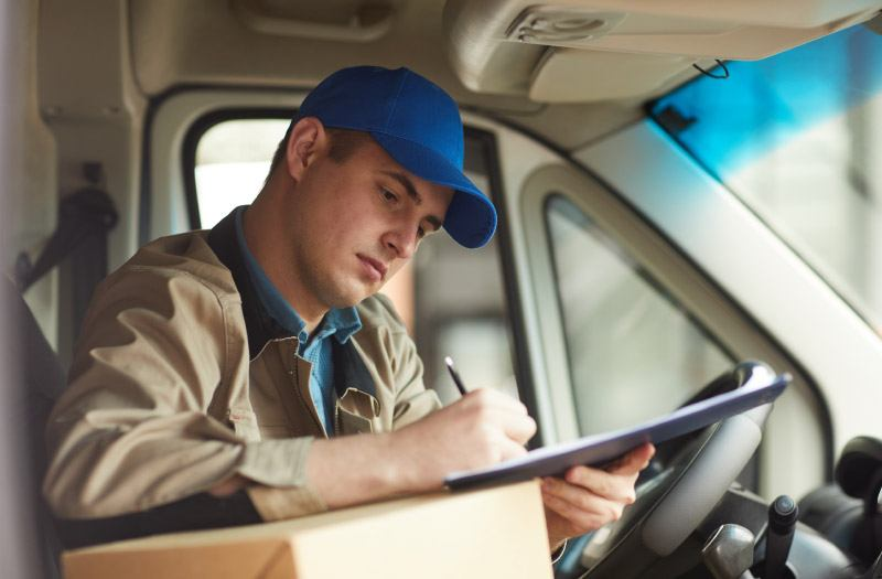 Young male delivery driver filling out form while sitting in van with package