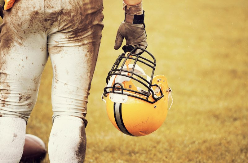 close-up of football player from behind holding helmet