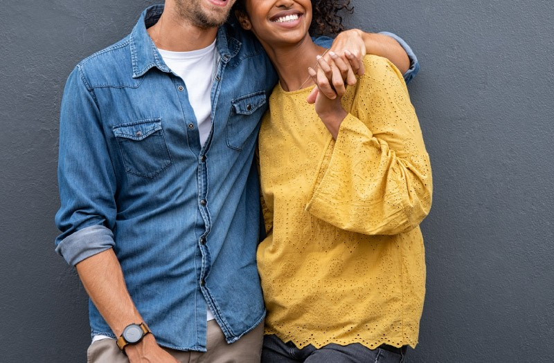 inter-racial couple with arms around each other