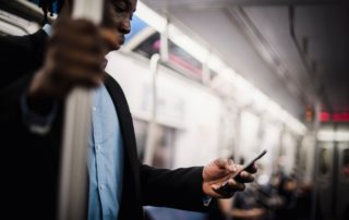 Black man using mobile while commuting by train